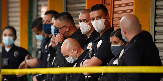 Los Angeles Police Department officers stand at the scene of a structure fire that injured multiple firefighters, according to a fire department spokesman, Saturday, May 16, 2020, in Los Angeles. (Associated Press)