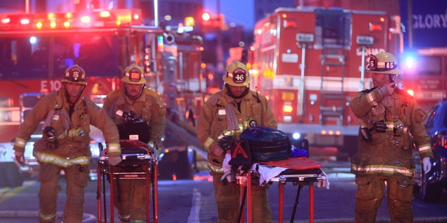 Los Angeles Fire Department firefighters push ambulance cots at the scene of a structure fire that injured multiple firefighters, according to a fire department spokesman, Saturday, May 16, 2020, in Los Angeles. (Associated Press)