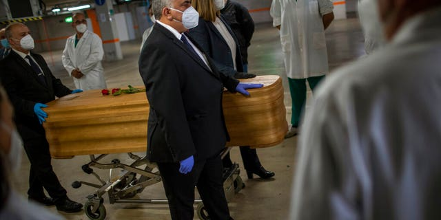 Mortuary service workers on Sunday carrying the coffin of the last COVID-19 victim stored at an underground parking garage that was turned into a morgue, at the Collserola funeral home in Barcelona, Spain. (AP Photo/Emilio Morenatti)