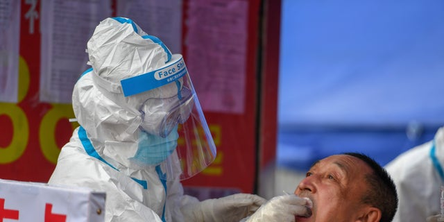 A medical worker collects a sample for COVID-19 testing at the Tongji community in Shulan in northeastern China's Jilin Province on Sunday. Authorities have tightened restrictions in parts of Jilin province in response to a local cluster. (Zhang Nan/Xinhua via AP)