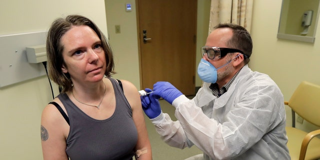 A pharmacist gives the first shot in the first-stage safety study clinical trial of a potential vaccine for COVID-19, the disease caused by the new coronavirus in Seattle on March 16, 2020. The vaccine by Cambridge, Massachusetts-based Moderna Inc., generated antibodies similar to those seen in people who have recovered from COVID-19 in a study volunteers who were given either a low or medium dose. (AP Photo/Ted S. Warren, File)