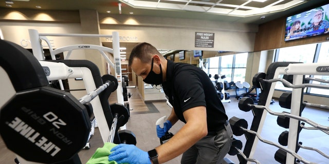 digital products Jason Nichols, facilities operation manager, disinfects equipment at the Life Time Biltmore as it opens for business after being closed due to the coronavirus, May 18, 2020, in Phoenix. (Associated Press)