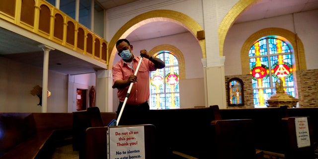 Juan Arriola helps clean and sanitize pews following an in-person Mass at Christ the King Catholic Church in San Antonio, May 19. San Antonio parishes that have been closed due to the COVID-19 pandemic began reopening their doors to in-person services. (AP Photo/Eric Gay)