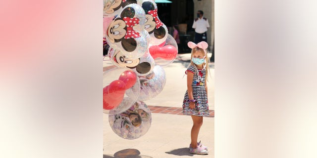A girl gazes at Mickey Mouse balloons at Disney Springs in Orlando on May 20. Walt Disney World's shopping and dining complex is beginning the first phase of getting back to business. (Stephen M. Dowell/Orlando Sentinel via AP)