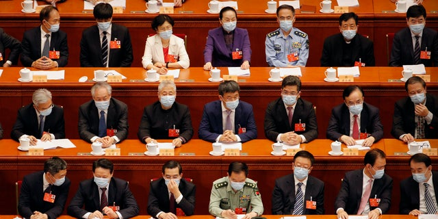 Delegates wearing face masks to protect against the spread of the new coronavirus wait for the start of the opening session of the Chinese People's Political Consultative Conference (CPPCC) at the Great Hall of the People in Beijing, Thursday, May 21, 2020. (AP Photo/Andy Wong, Pool)
