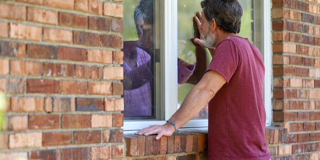 Jack Campise talks with his mother, Beverly Kearns, through her apartment window at the Kimberly Hall North nursing home, Thursday, May 14, 2020 in Windsor, Conn. The coronavirus has had no regard for health care quality or ratings as it has swept through nursing homes around the world, killing efficiently even in highly rated care centers. Preliminary research indicates the numbers of nursing home residents testing positive for the coronavirus and dying from COVID-19 are linked to location and population density — not care quality ratings.