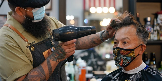 Luis Lopez wears a face mask while giving a hair cut to Alexander Chin at Orange County Barbers Parlor on May 27. (AP Photo/Ashley Landis)