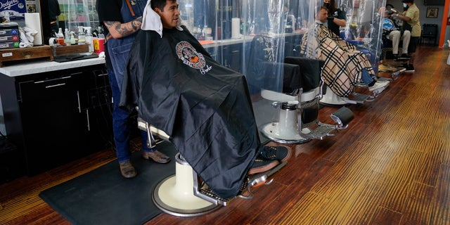 Louie Ruvalcaba gets a hair cut from Saul Arvizu as other customers get their hair cut at Orange County Barbers Parlor on May 27 in Huntington Beach, Calif. (AP Photo/Ashley Landis)