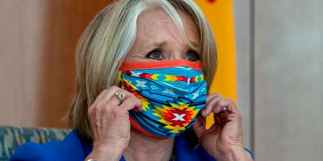 New Mexico Gov. Michelle Lujan Grisham removes her face mask at the start of an update on the COVID-19 outbreak in New Mexico and the State's effort to limit the impact of the disease on residents, during a news conference at the State Capitol on Wednesday. (Eddie Moore/The Albuquerque Journal via AP)