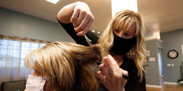 Tisha Fernhoff cuts Lisa Froling's hair at the Beauty Bar Salon in Auburn, Calif. on May 27. Froling was the salon's first client after reopening Wednesday morning. (AP Photo/Rich Pedroncelli)