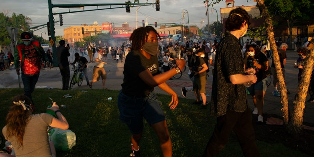 A protester runs away from where police deployed chemical irritants near the 3rd Precinct building in Minneapolis on May 27, during a protest against the death of George Floyd in Minneapolis police custody earlier in the week. (Christine T. Nguyen/Minnesota Public Radio via AP)
