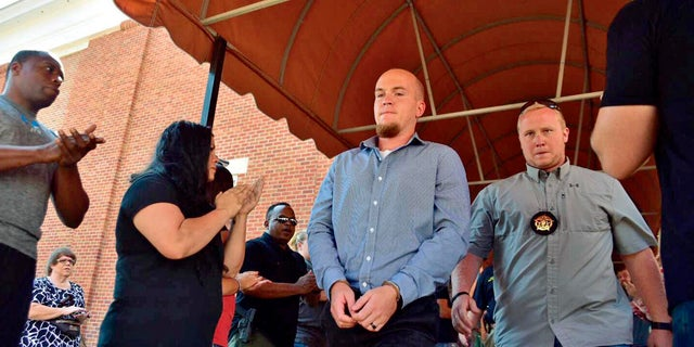 A file image of former police officer Canyon Boykin, center, being led from the Lowndes County Courthouse in handcuffs while people applauded in Columbus, Miss.