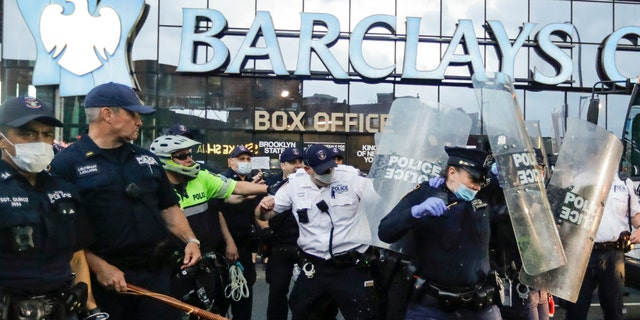 Police officers protect themselves with shields as protesters throw debris during a rally at the Barclays Center over the death of George Floyd, a black man who was in police custody in Minneapolis Friday, May 29, 2020, in the Brooklyn borough of New York. Floyd died after being restrained by Minneapolis police officers on Memorial Day. (AP Photo/Frank Franklin II)