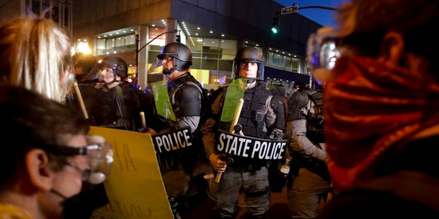 Protesters stand in front of Kentucky State Police officers as they protest the deaths of George Floyd and Breonna Taylor, Friday, May 29, 2020, in Louisville, Ky. Breonna Taylor, a black woman, was fatally shot by police in her home in March.