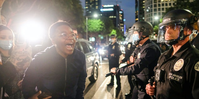 A protester yells at police during a protest for George Floyd, in downtown Los Angeles, Friday, May 29, 2020. (AP Photo/Ringo H.W. Chiu)