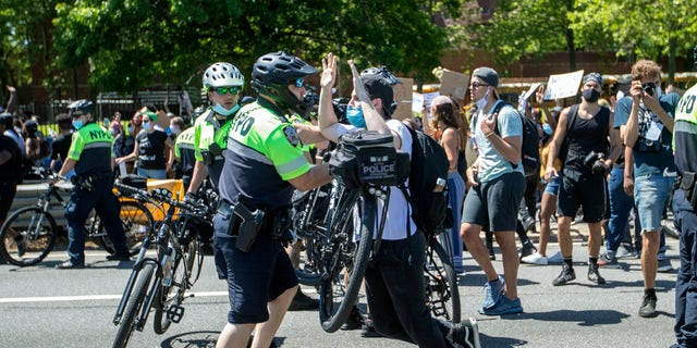 A police officer uses his bicycle to shove a demonstrator on the F.D.R. during a solidarity rally for George Floyd, Saturday, May 30, 2020, in New York. Floyd died after Minneapolis police officer Derek Chauvin pressed his knee into his neck for several minutes even after he stopped moving and pleading for air. (AP Photo/Mary Altaffer)