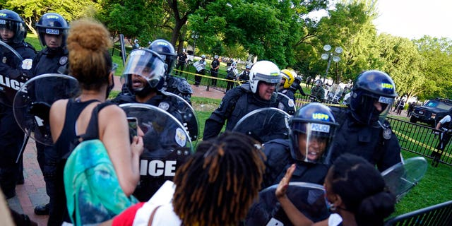 Demonstrators vent to police in riot gear as they protest the death of George Floyd, Saturday, May 30, 2020, near the White House in Washington. Floyd died after being restrained by Minneapolis police officers. (AP Photo/Evan Vucci)