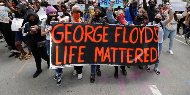 Protesters hold signs as they march during a protest over the death of George Floyd in Chicago, Saturday, May 30, 2020.