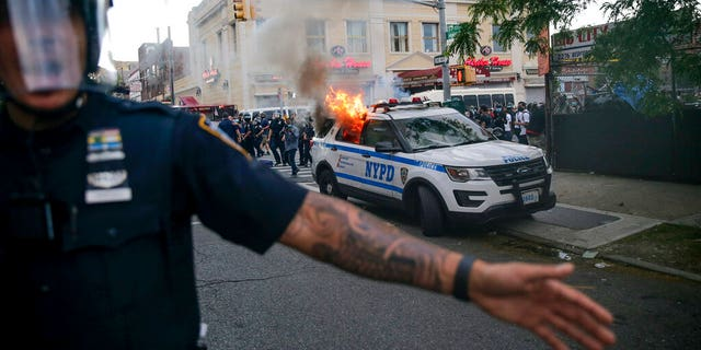 New York Police officers push back protesters as a police car burns during a demonstration, Saturday, May 30, 2020, in the Brooklyn borough of New York.