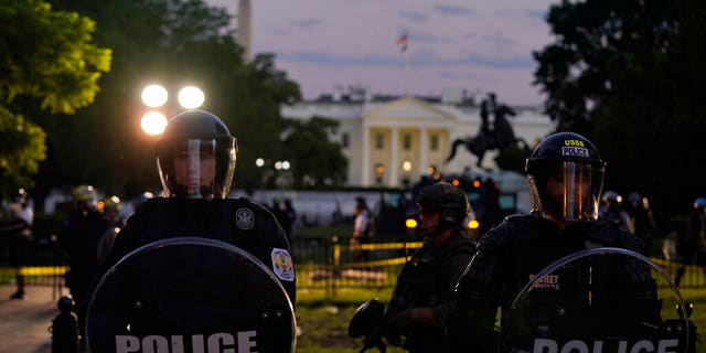 Police in riot gear stand in front of the White House as demonstrators gather to protest the death of George Floyd, Saturday, May 30, 2020, outside the White House in Washington. Floyd died after being restrained by Minneapolis police officers.