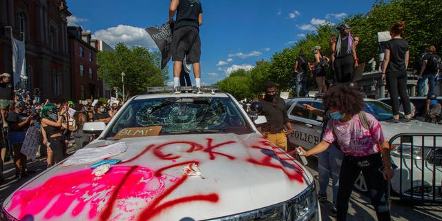 Demonstrators stand on U.S. Secret Service vehicles, one with a broken windshield, near the White House on Saturday, May 30, 2020 (AP Photo/Manuel Balce Ceneta)