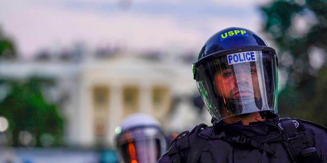 Police in riot gear stand in front of the White House as demonstrators gather to protest the death of George Floyd, Saturday, May 30, 2020, outside the White House in Washington. (AP Photo/Evan Vucci)