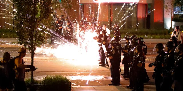 A firework explodes by a police line as demonstrators gather to protest the death of George Floyd, Saturday, May 30, 2020, near the White House in Washington. (AP Photo/Alex Brandon)