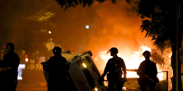 Police stand near a overturned vehicle and a fire as demonstrators protest the death of George Floyd, Sunday, May 31, 2020, near the White House in Washington. Floyd died after being restrained by Minneapolis police officers. (AP Photo/Alex Brandon)