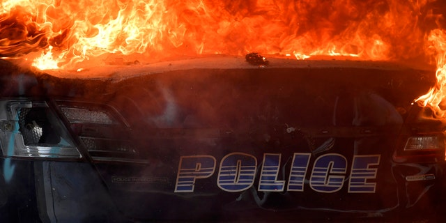 An Atlanta Police Department vehicle burns during a demonstration against police violence, Friday, May 29, 2020 in Atlanta.