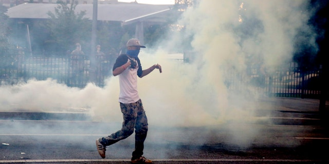 Demonstrators protest in a fog of gas that the Atlanta Police launched at a crowd, Saturday, May 30, 2020 in Atlanta.