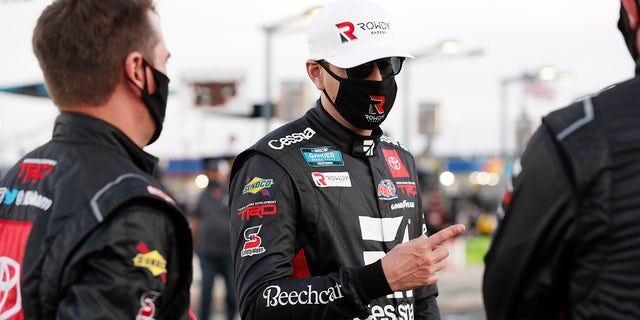 Kyle Busch, center, waits for the start of a NASCAR Truck Series auto race at Charlotte Motor Speedway Tuesday, May 26, 2020 in Concord, N.C. (AP Photo/Gerry Broome)