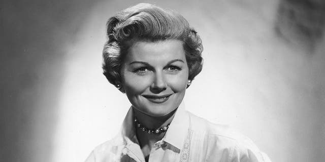 circa 1955: Studio portrait of American actor Barbara Billingsley seated and wearing a white blouse with lace stitching over a black ruffled skirt. She played June Cleaver in the television show 'Leave it to Beaver.' (Photo by CBS Photo Archive/Getty Images)