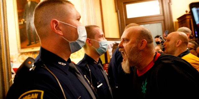 Protestors tried to enter the Michigan House of Representative chamber and were being kept out by the Michigan State Police at the State Capitol in Lansing, on April 30. The group was upset with Michigan Gov. Gretchen Whitmer's mandatory closure to curtail Covid-19. (JEFF KOWALSKY/AFP via Getty Images)