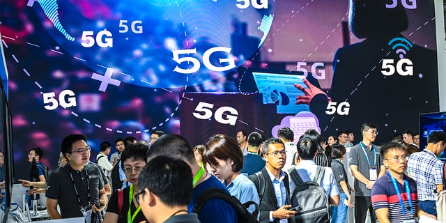 Visitors in action in front of a 5G advertisement during Mobile World Congress (MWC) Shanghai 2019 at Shanghai New International Expo Center on June 27, 2019 in Shanghai, China. (Photo by Gao Yuwen/Visual China Group via Getty Images)