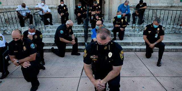 Police officers kneel during a rally in Coral Gables, Florida on May 30, 2020, in response to the recent death of George Floyd, an unarmed black man who died while being arrested and pinned to the ground by a Minneapolis police officer. (Photo by Eva Marie UZCATEGUI / AFP)