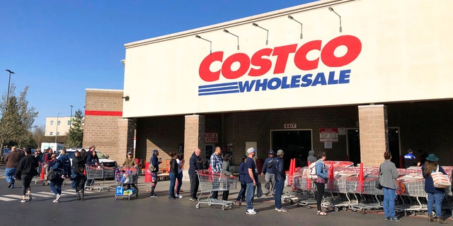 Shoppers line up to enter a Costco store, in March 2020, in Tacoma, Washington. (AP Photo/Ted S. Warren)