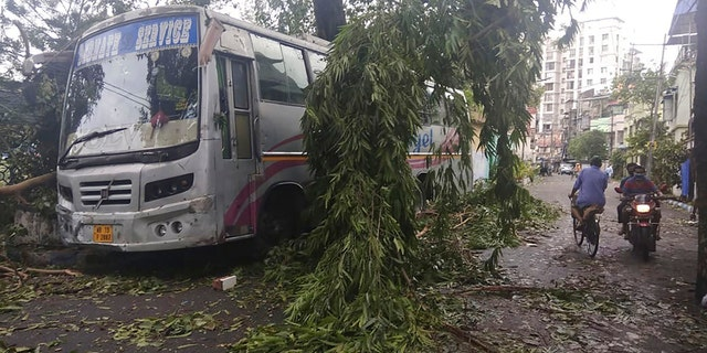 Commuters move past a tree branch precariously hanging after cyclone Amphan hit the region, in Kolkata, India, May 21. A powerful cyclone that slammed into coastal India and Bangladesh has left damage difficult to assess Thursday. (AP Photo/Bikas Das)