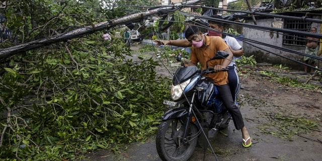 Motorists make their way through damaged cables and a tree branch fallen in the middle of a road after Cyclone Amphan hit the region in Kolkata, India, May 21. (AP Photo/Bikas Das)