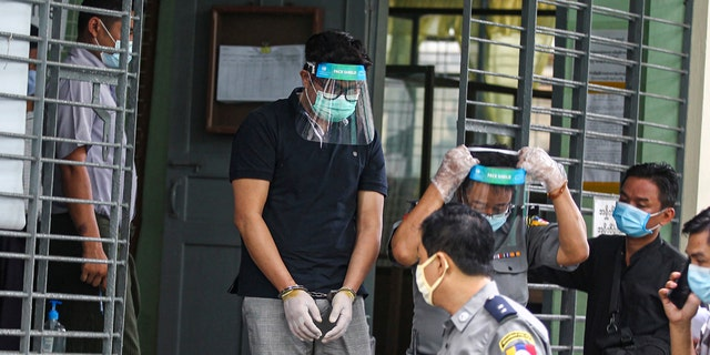 Canadian pastor David Lah covered with face shield and mask is escorted by police men as he leaves from a township court after his first court appearance Wednesday, May 20, 2020, in Yangon, Myanmar. Lah attends a court hearing related to charges filed against him for allegedly organizing public Christian activities in Yangon back in April, after the regional government banned mass gatherings in mid-March to curb the spread of the coronavirus. (AP Photo/Thein Zaw)