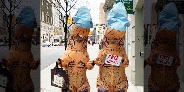 """In videos of the dinosaur duo, the pair are holding up signs advertising """"free masks"""" and holding out bags for people to help themselves."""