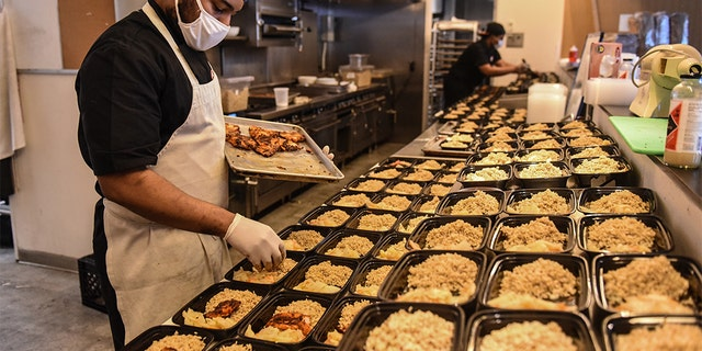 Employees work to create to-go donation meals for a company called Collective Fare in the Brownsville neighborhood in the Brooklyn borough in New York City.