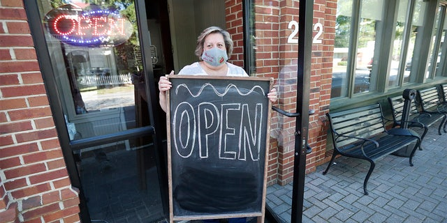 Mary Spoto, general manager of Madison Chop House Grille, places a sign outside the restaurant as she and her staff prepare to shift from take out only to dine-in service Monday, April 27, 2020, in Madison, Ga. (Associated Press)