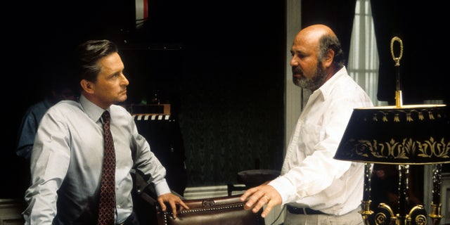 Michael Douglas (L) listening to director Rob Reiner in between scenes from the film 'The American President.'