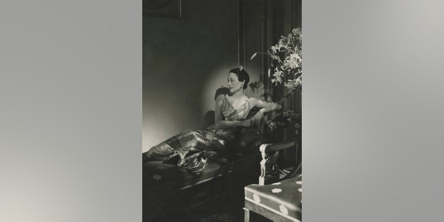 gardening The Duchess of Windsor wearing a gown, reclining on a chaise.
