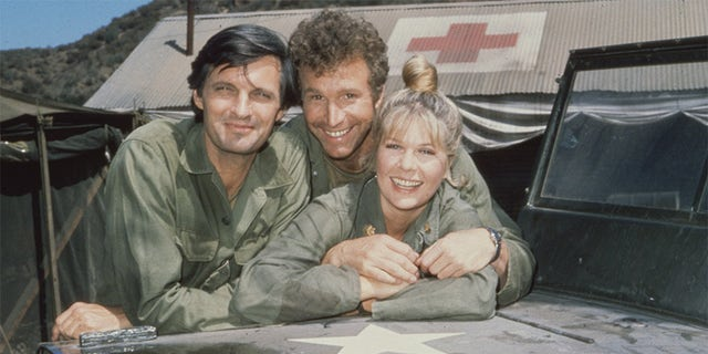 Portrait of, from left, American actors Alan Alda, as Captain Benjamin Hawkeye Pierce, Wayne Rogers, as Captain Trapper John McIntyre, and Loretta Swit, as Major Margaret Houlihan, on the television series 'M*A*S*H,' California, 1972.