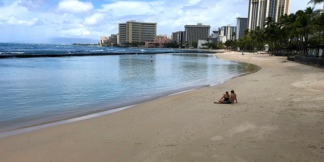 March 28, 2020: A couple sits on an empty section of Waikiki Beach in Honolulu. Hawaii law enforcement authorities are cracking down on rogue tourists who are visiting beaches, jetskiing, shopping and generally flouting strict requirements that they quarantine for 14 days after arriving.