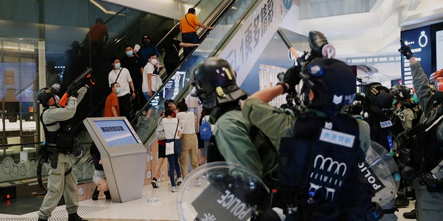 Riot police raise their pepper spray projectile inside a shopping mall as they disperse anti-government protesters during a rally, in Hong Kong, China, on Sunday. (Reuters)