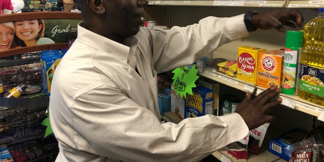 Burnell Cotlon stocks shelves in 'Burnell's Lower 9th Ward Market.' He's had to give away food to people in the community who are struggling to make it through the coronavirus pandemic. (Fox News/Charles Watson)