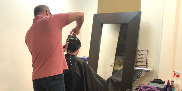 Hairstylist John Bryant reopens his salon and begins taking limited clients.