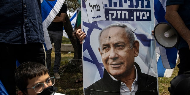 An Israeli protester wears a mask amid concerns over the country's coronavirus outbreak looks on a poster of Prime Minister Benjamin Netanyahu during a protest by supporters of Netanyahu in front of Israel's Supreme Court in Jerusalem, Sunday, May 3, 2020. (AP Photo/Tsafrir Abayov)